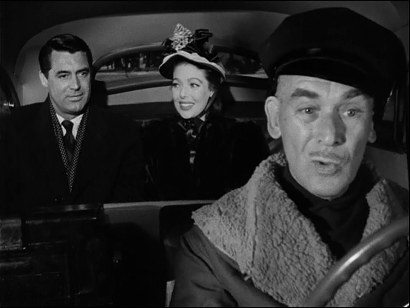 Cary Grant and Loretta Young listen to James Gleason gas on as Sylvester, the loquacious cabbie.